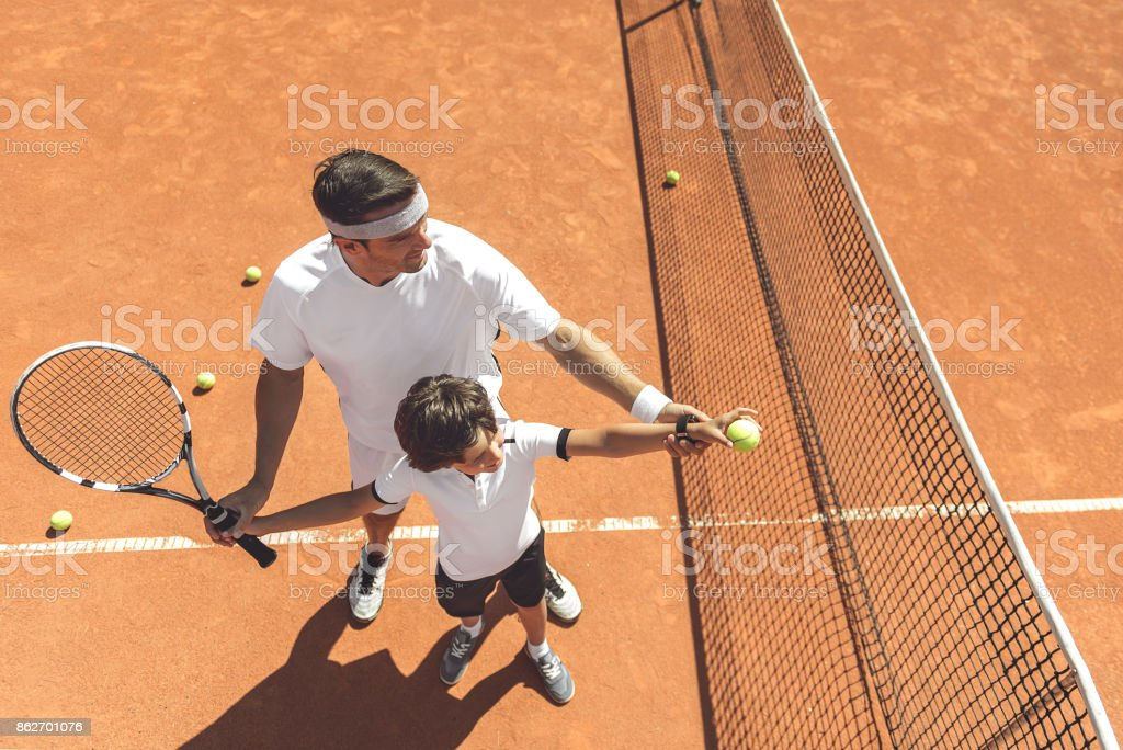 Father is teaching his son to make pitch in right way. He standing...