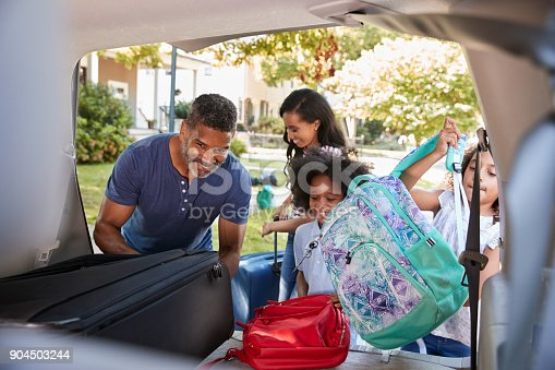 istock Family Leaving For Vacation Loading Luggage Into Car 904503244