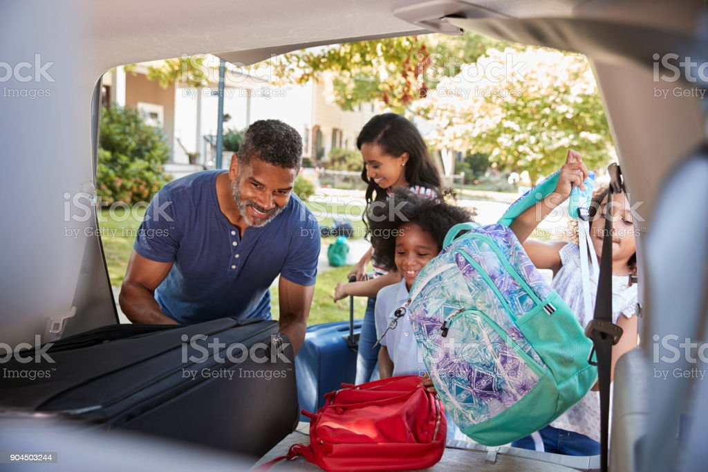 Family Leaving For Vacation Loading Luggage Into Car stock photo