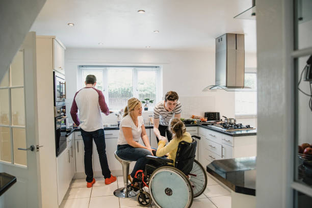 Family Life in the Kitchen with Disabled Daughter Mature mum and her son are interacting with her disabled daughter who is sitting in a wheelchair. The father is standing behind them preparing lunch. als stock pictures, royalty-free photos & images