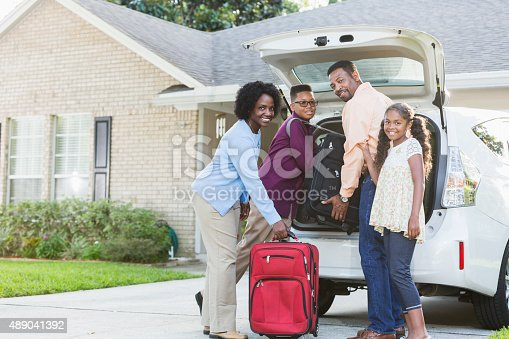 istock Family loading luggage into car going on vacation 489041392
