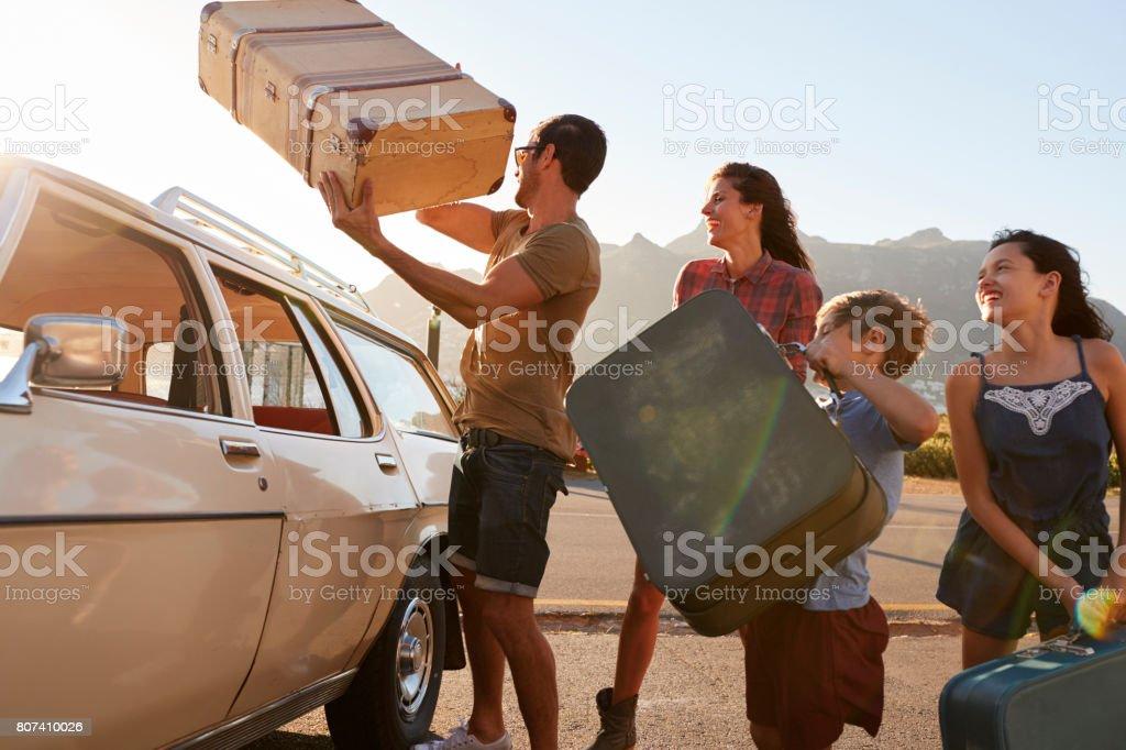 Familia cargando equipaje en coche techo listo para el viaje - foto de stock