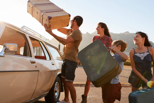 family loading luggage onto car roof rack ready for road trip - family vacation stock photos and pictures
