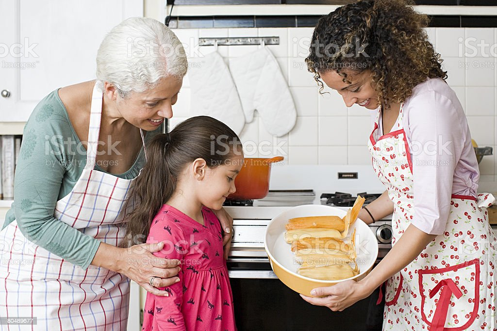 A family looking at a dish of tamales stock photo