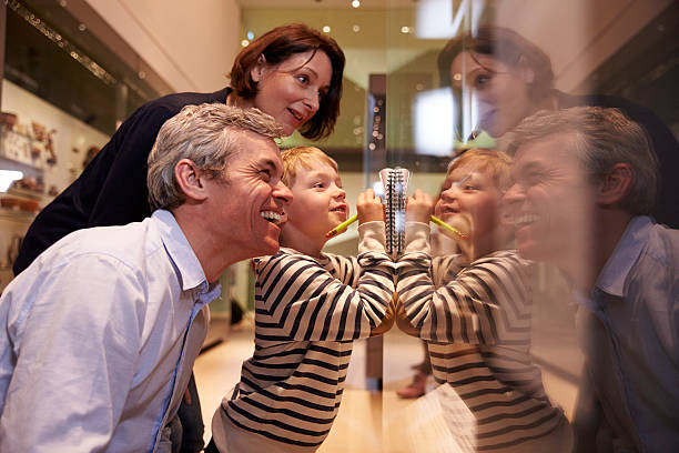 family looking at artifacts in glass case on trip - museum stockfoto's en -beelden