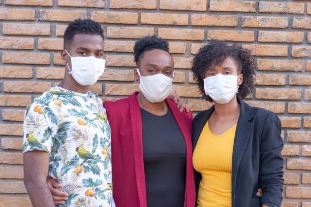 family looking at camera using protective mask - afro latino mask imagens e fotografias de stock