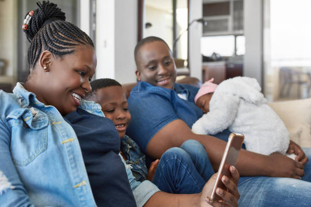 Family looking at mobile phone on sofa at home stock photo
