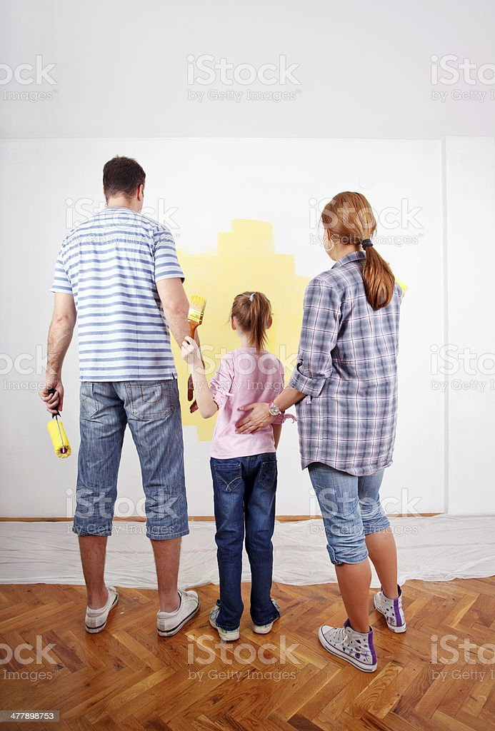 Family looking at paint sample on the wall. royalty-free stock photo
