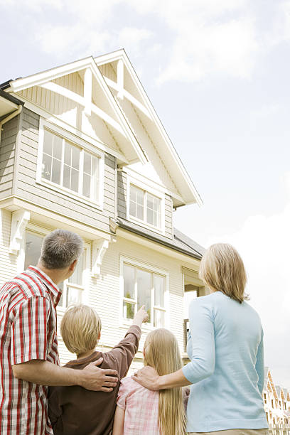 Family looking at surburban home in neighborhood stock photo