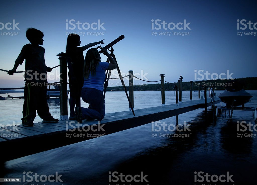 family looking at the strars from a jetty stock photo
