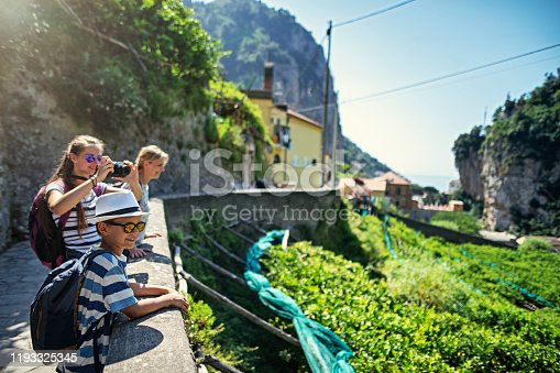 Family hiking in Amalfi coast, Campania, Italy. They are looking at the mountains and Amalfi visible in the background. Nikon D850