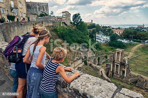 Mother and kids tourists sightseeing beautiful Italian town of Volterra. Family is admiring roman theatre from the city walls.