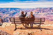 Stock photograph of a family with one child looking at view in Grand Canyon National Park, South Rim, USA on a sunny day.