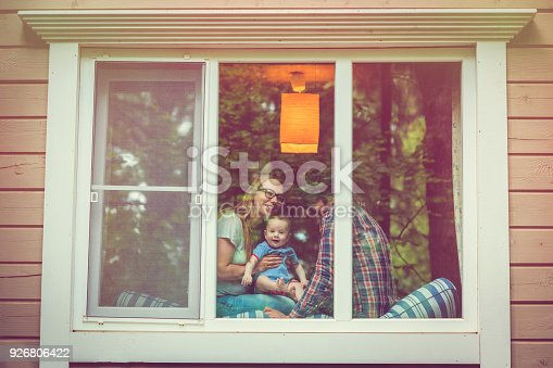 Parents with their baby through a window
