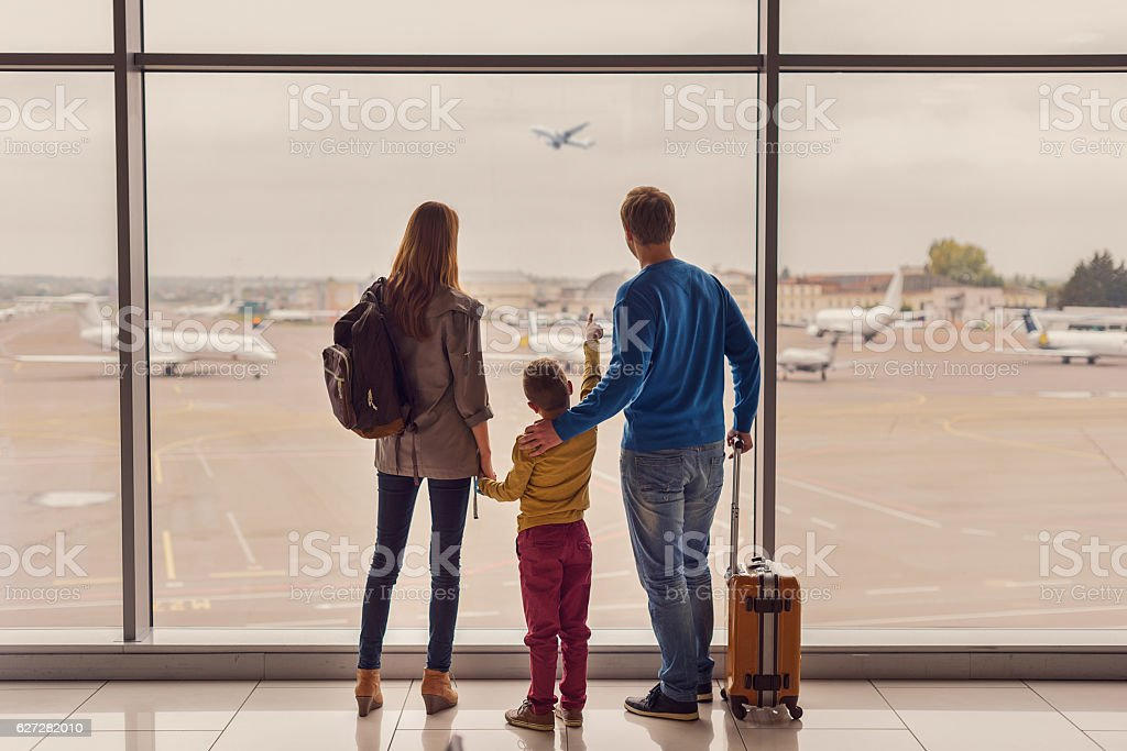 Family looking out window at airport stock photo