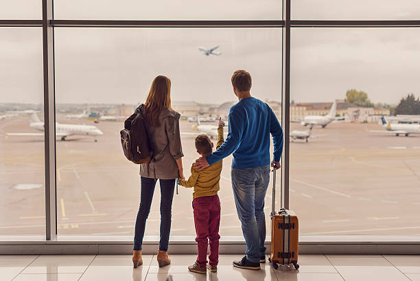 family looking out window at airport - travel destinations stock photos and pictures