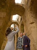 istock Family looks up and takes photo of ancient archways 1304054522