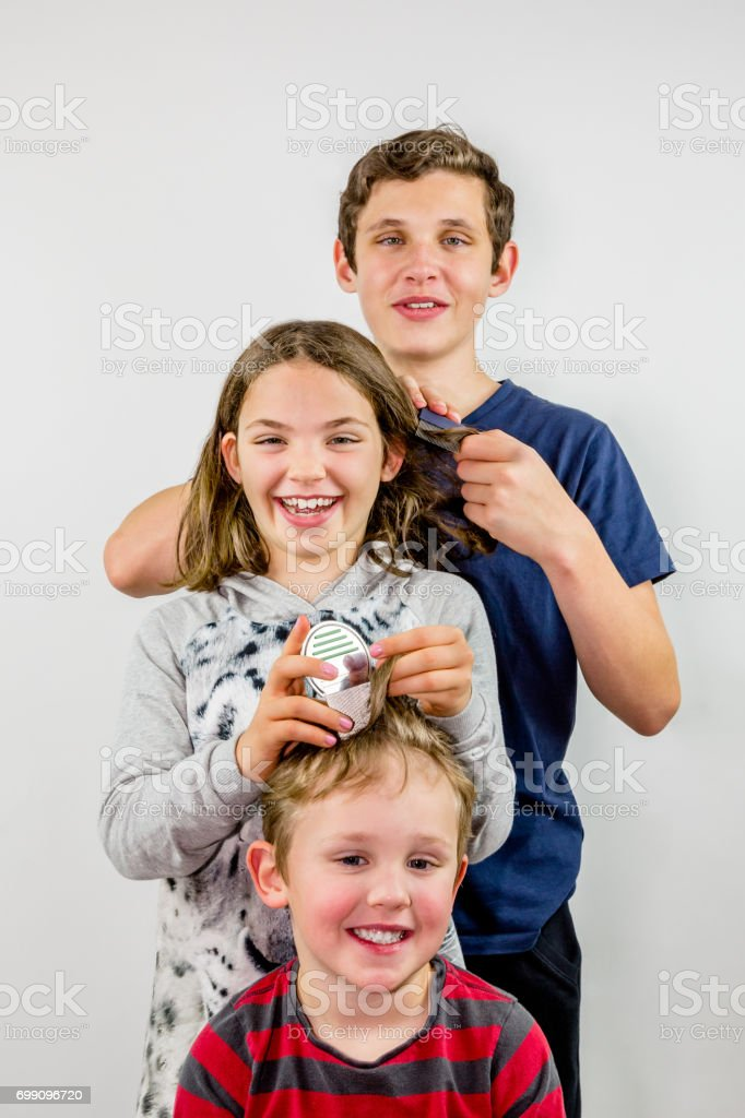 Family louse treatment. Three children comb each others hair to look for head lice. royalty-free stock photo