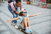 Mother and daughter on street enjoy in beautiful day and have fun on skateboards, mother push in back daughter that sitting on skate. They love to spend day together in favorite activities.