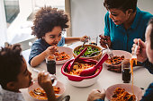 Cute mixed race family having lunch at home.