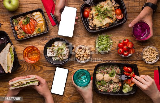 Food delivery. Family lunch at home with healthy meal in take away boxes, blank screen for advertisement