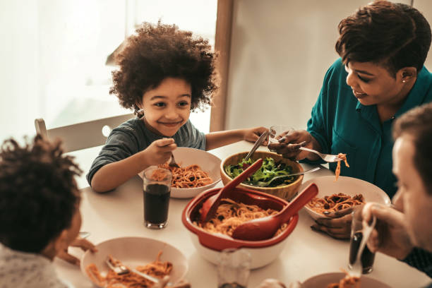Family Lunch Cute family having lunch together. spaghetti stock pictures, royalty-free photos & images
