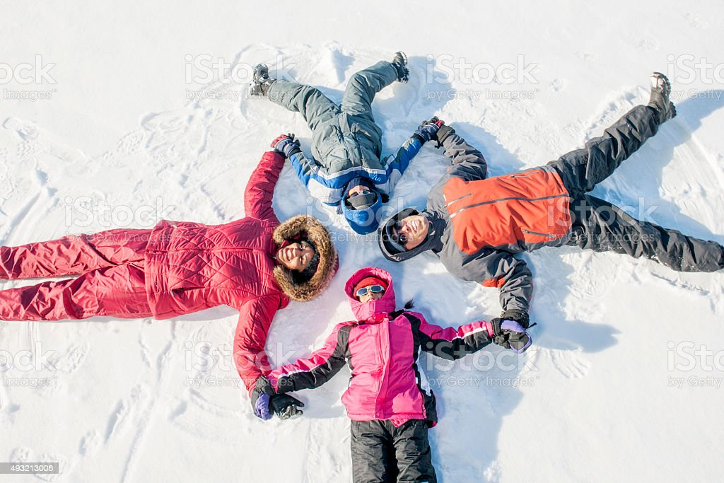 Family Lying in a Circle in the Snow stock photo
