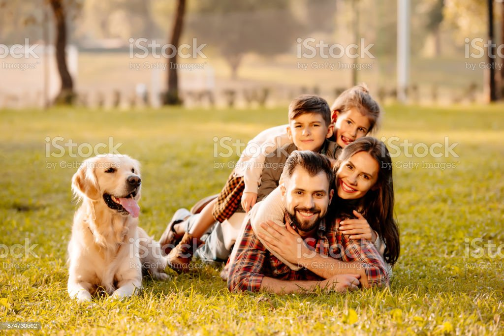 family lying in pile on grass stock photo