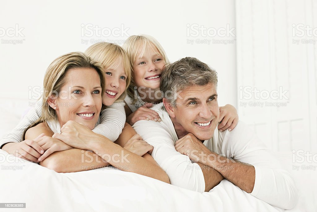 Family Lying on a Bed and Smiling royalty-free stock photo