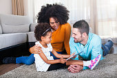 istock Family lying on carpet and playing games on digital tablet 540611890