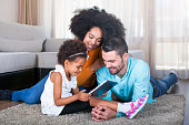 istock Family lying on carpet and playing games on digital tablet 540611916