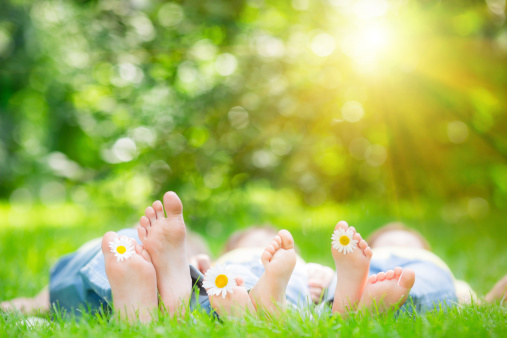 Family lying on grass outdoors in spring park
