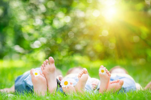 familie liegen auf dem grass - kinderfüße stock-fotos und bilder