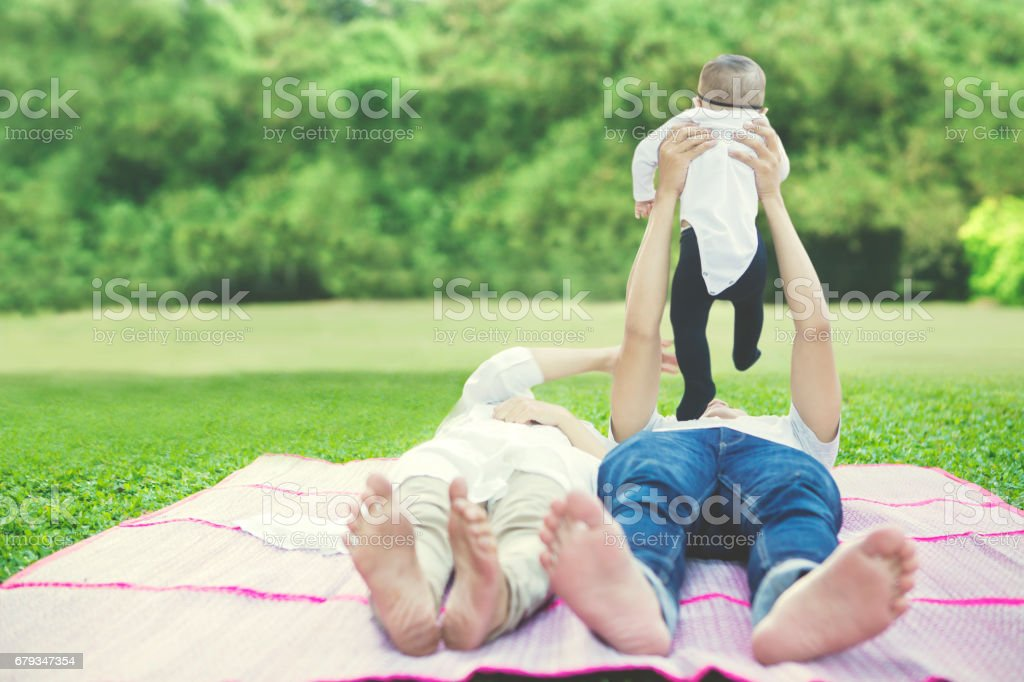 Family lying on mat at field stock photo