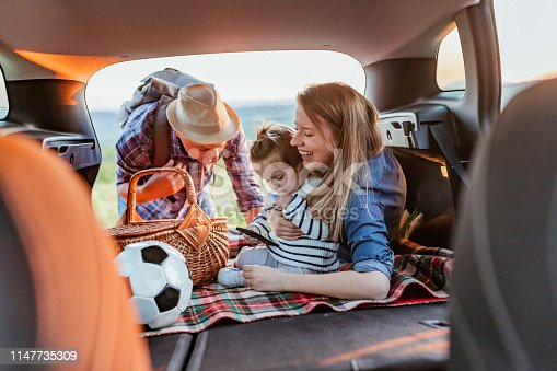 Photo of Happy family getting ready for a road trip on a sunny day.  Photo of Beautiful woman and handsome husband with a child of two years in the car are going to have a trip. Happy family on a road trip in their car. Mom, Father, and daughter are traveling by car. Summer ride by automobile. Vacation, Travel - family ready for the travel for summer vacation. Vacations And Tourism Concept, Little Boy in the rental car with his brown hair mother and father.