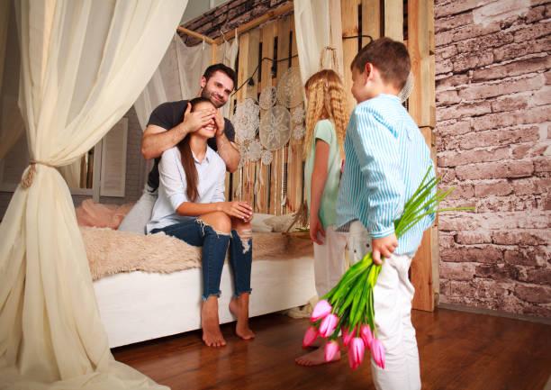 familie macht überraschung mutter schenken von blumen - lila, grün, schlafzimmer stock-fotos und bilder