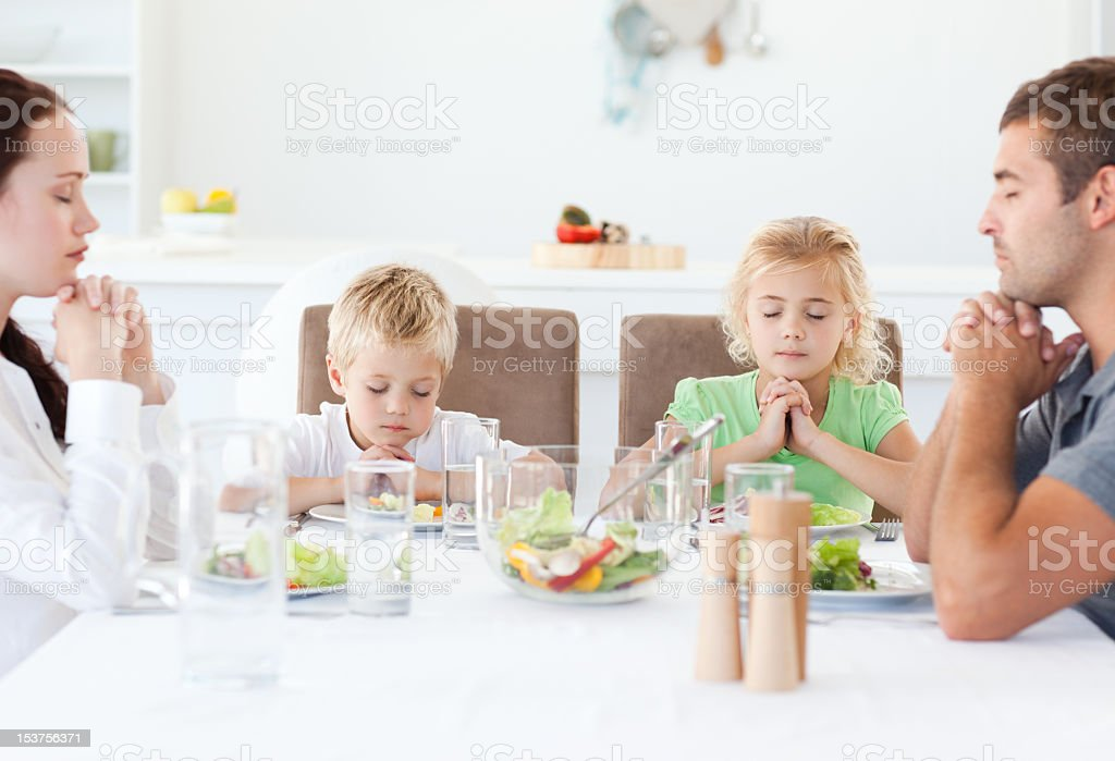 Family making a blessing before the meal stock photo