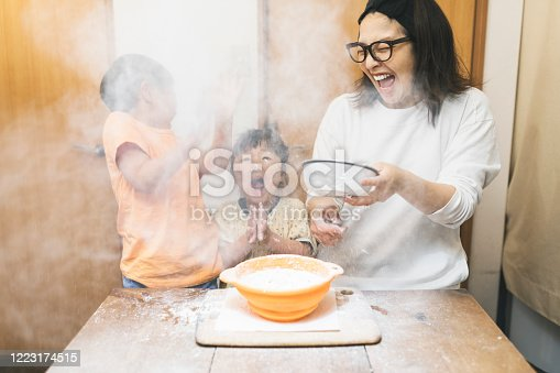 Flour is swirling in the air and Asian family are surprised  while kneading flour.