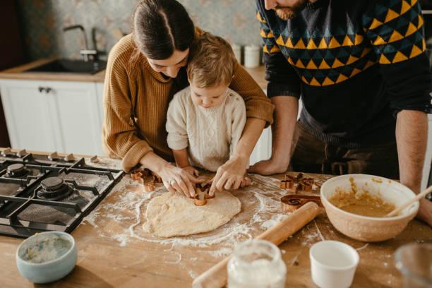 familj att göra cookies - baka bildbanksfoton och bilder