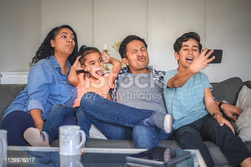 Playful family making faces while taking selfie using mobile phone. Parents and children are enjoying weekend together. They are sitting on sofa at home.