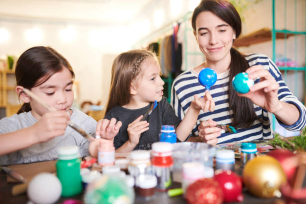 Family  Making Handmade Ornaments Portrait of two little children making handmade Christmas decorations in crafting class with smiling female teacher craft stock pictures, royalty-free photos & images