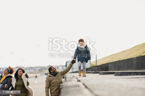 A grandfather holding his grandson's hand as he walks alongside him on a walk with family.