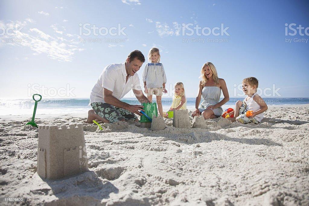 Family making sand castles on beach stock photo