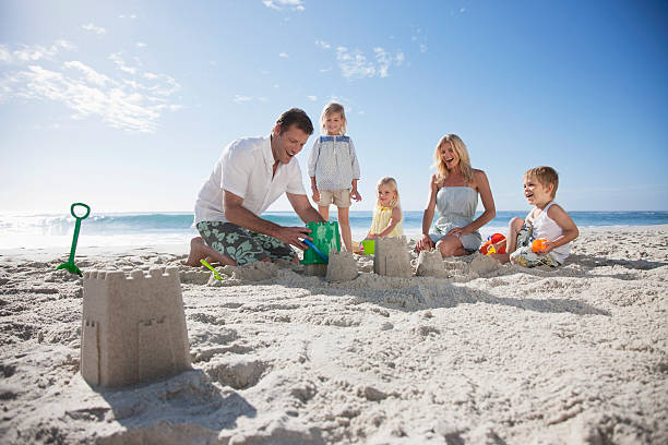 Family making sand castles on beach stock photo