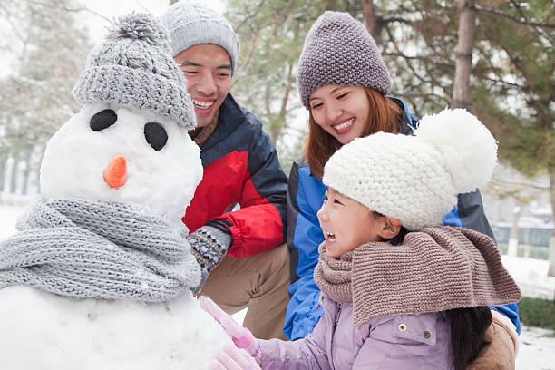 familie machen schneemann im winter - schneemann bauen stock-fotos und bilder