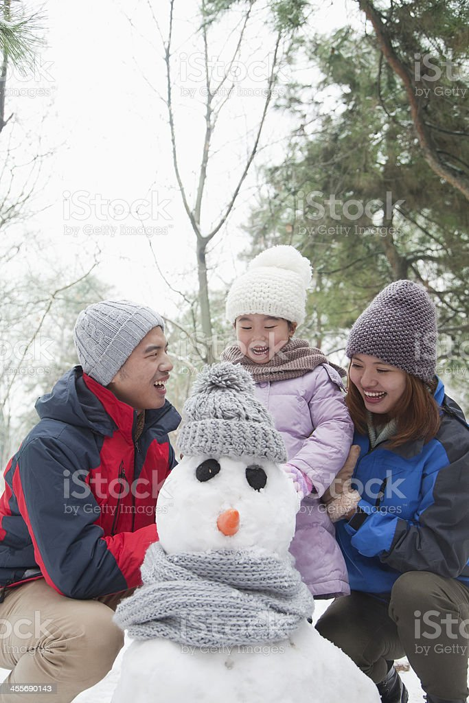 Family making snowman in winter stock photo