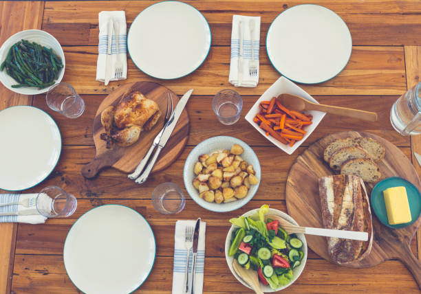 Family meal table with no people. Family meal table with no people. There is a full roast dinner on the table, with chicken, vegetables, salad and bread. carving knife stock pictures, royalty-free photos & images