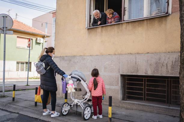 familiebijeenkomst tijdens een pandemie - raam bezoek stockfoto's en -beelden