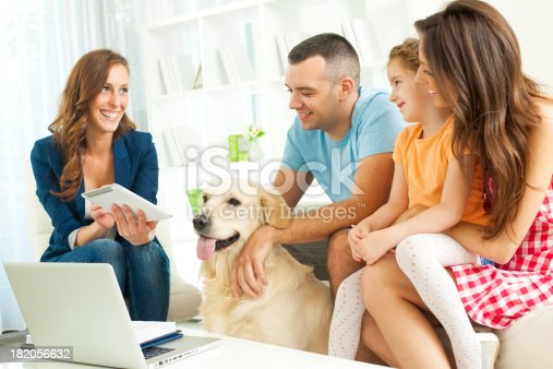 Family with two children Meeting With Financial Advisor presenting new bank offers and investments on digital tablet. Financial Advisor pointing with pen to some new offers. Selective focus to family.