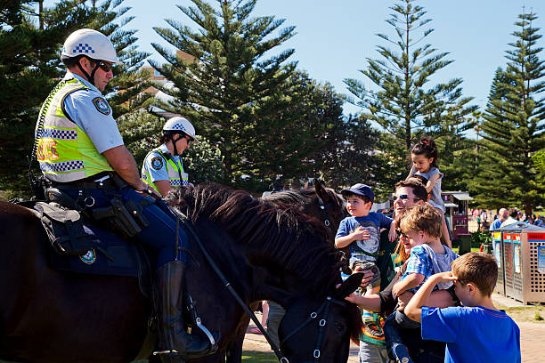 Family meets police horses and riders in Coogee, Sydney stock photo